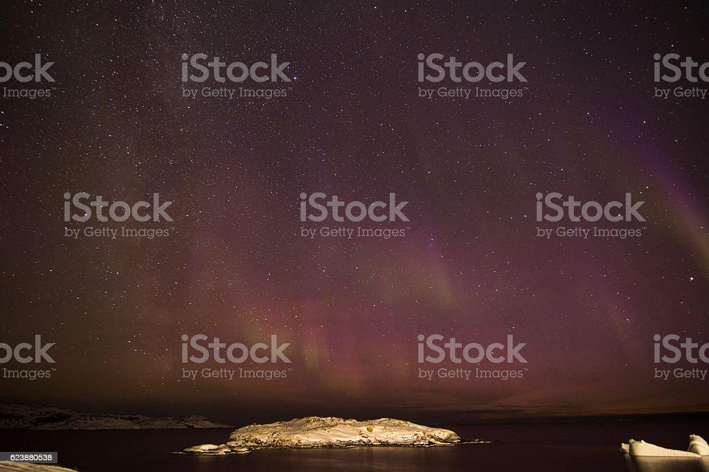 Pink Aurora Borealis over snow covered island stock photo