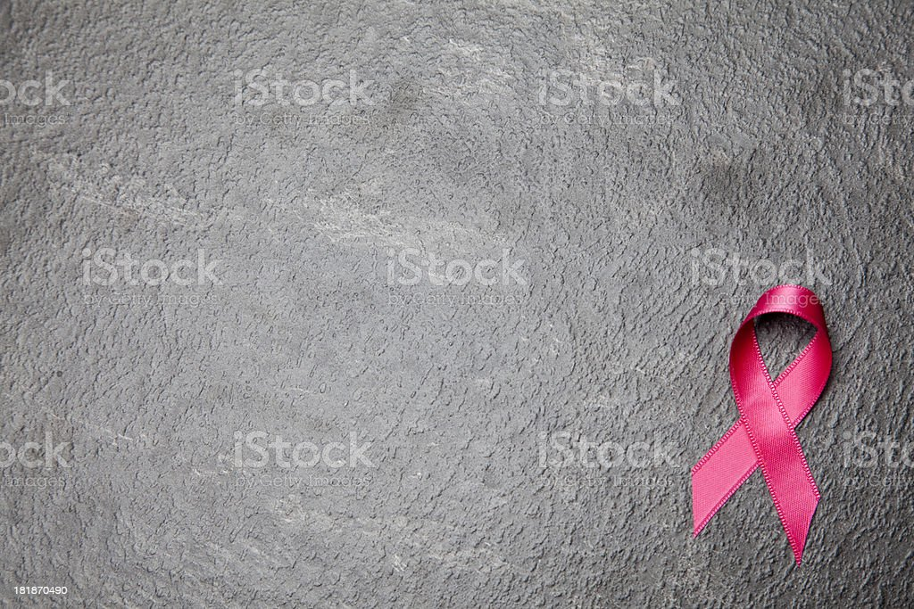 Pink awareness ribbon on slate background stock photo