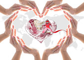 istock Pink awareness ribbon on world heart collaborative hands protection: Elements of this image furnished by NASA 1176442522
