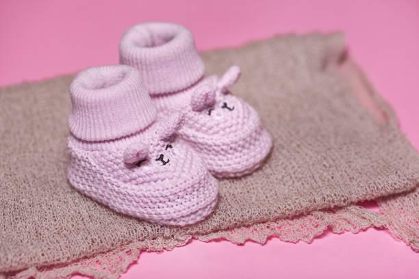 rosa babyschuhe als neugeborene kleidung, schwangerschaft und baby-dusche-konzept - babyschuhe nähen stock-fotos und bilder