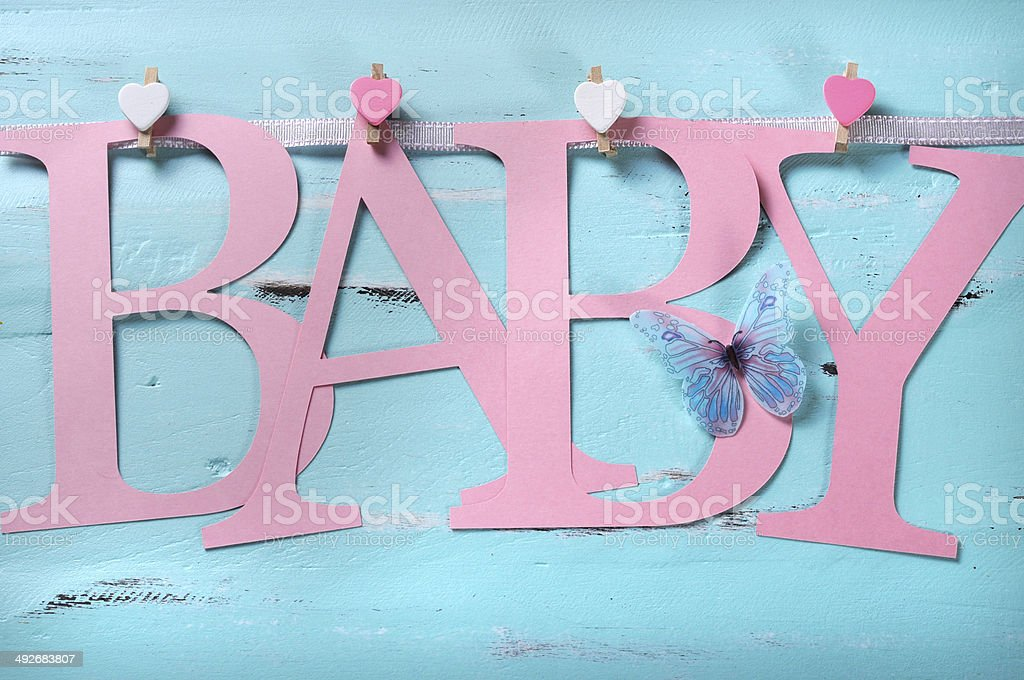 Pink baby girl letters bunting against a vintage aqua background stock photo