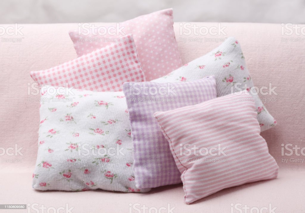 Lot of pink cozy pillows on the sofa