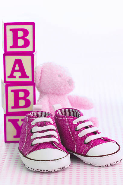 pink baby shoes with building blocks spelling out baby - its a girl stock photos and pictures