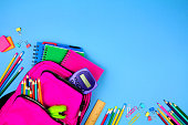 Pink backpack with corner border of school supplies against a blue paper background. Top view with copy space.