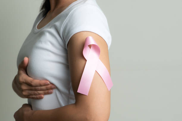 pink badge ribbon on woman arm to support breast cancer cause. breast cancer awareness concept stock photo