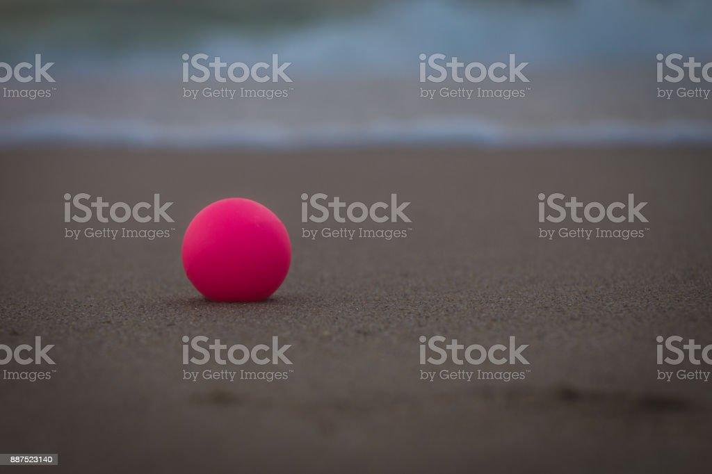 Pink ball on the beach, macro stock photo