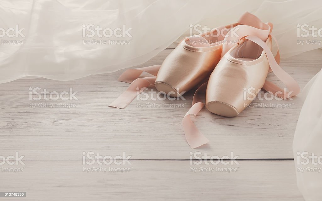 Pink ballet pointe shoes on white wood background stock photo