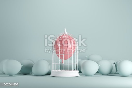 903520476 istock photo Pink balloon floating in white cage on pastel green background. minimal idea concept. 1002544808