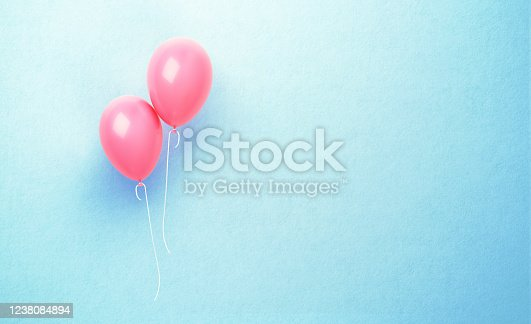 Pink balloons over blue background. Horizontal composition with copy space. Front view.