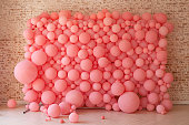 Pink balloons, pink bubbles beautiful birthday texture. Wall decor for a party. Decorated wall for the holiday. Cells under the microscope, macrocell division. Decorated brick wall with balloons.