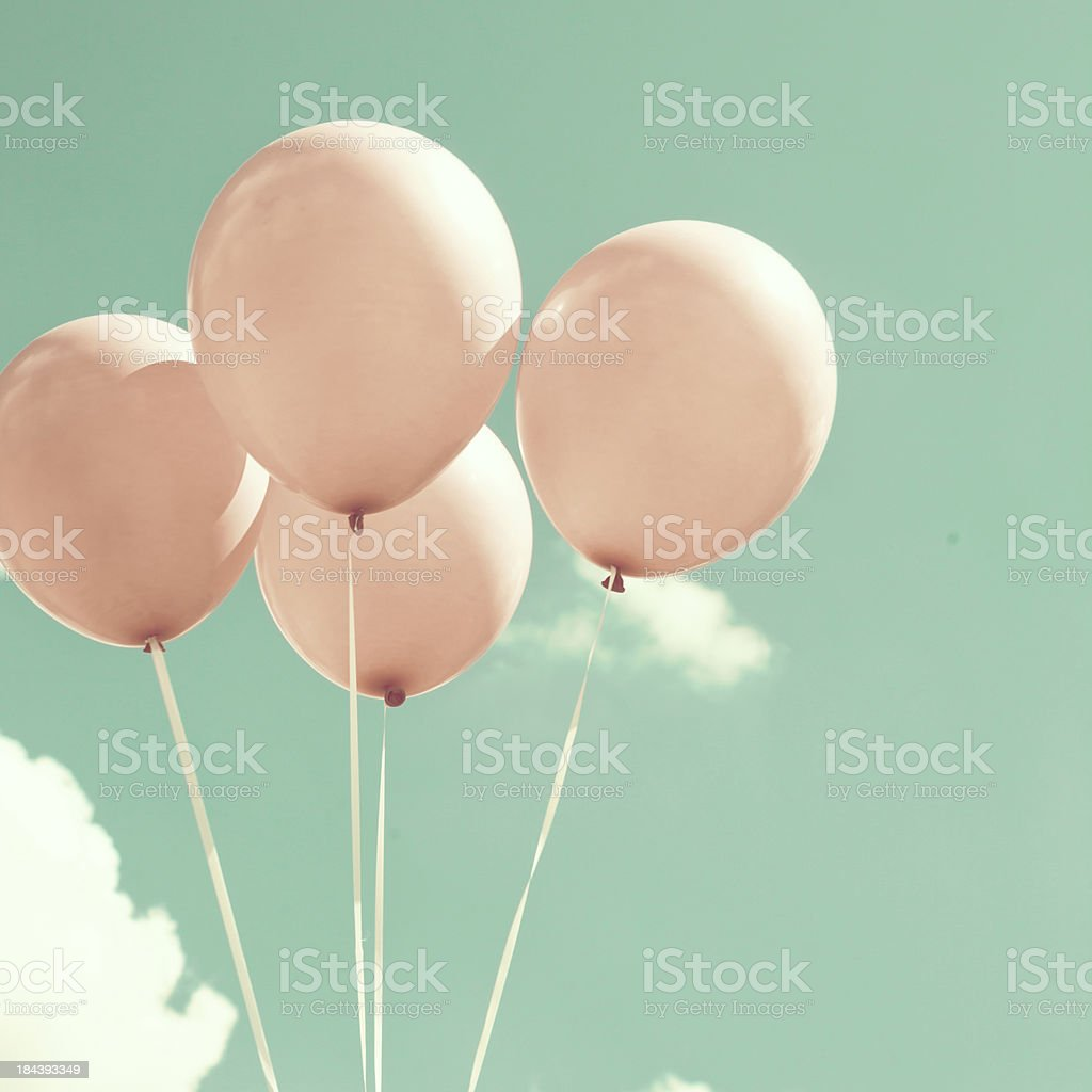 Pink balloons with sky in the background stock photo