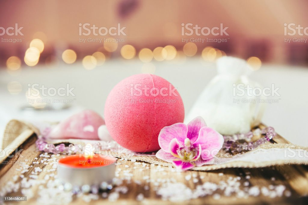 Pink bath ball with orchid flower, scented candle and bath salt on wooden tray in bath room. Therapy concept. Taking a relaxing bath. - Foto stock royalty-free di Accudire