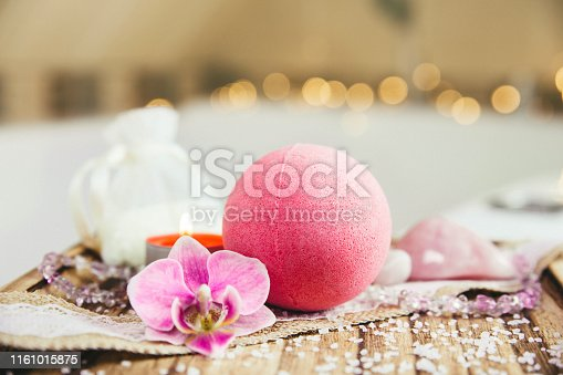 istock Pink bath ball with orchid flower, scented candle and bath salt on wooden tray in bath room. Therapy concept. Taking a relaxing bath. 1161015875