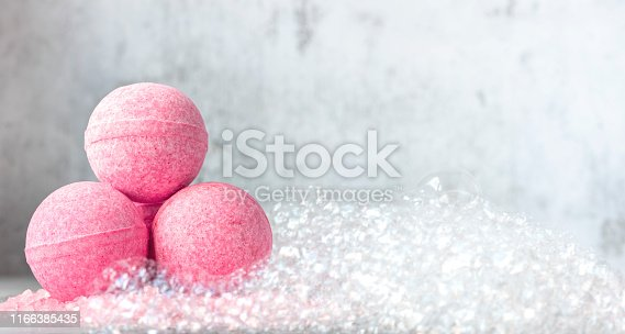 istock Pink bath balls on a background of soapy foam 1166385435