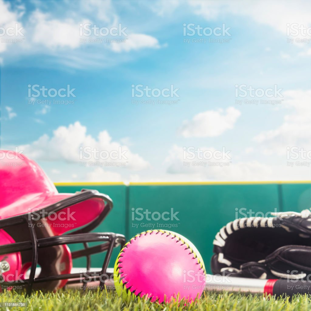 A low angle view of a pink and yellow softball along with an aluminum...