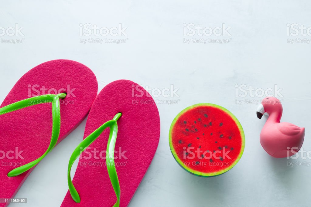 pink beach flip flops and squishy toy watermelon and flamingo on...