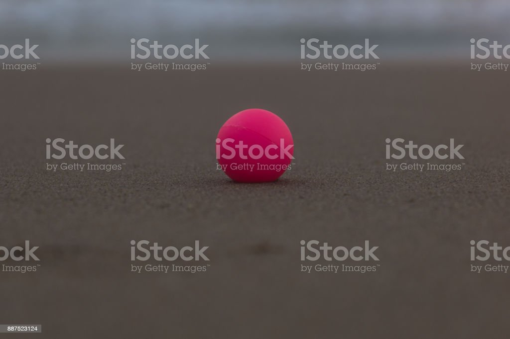 Pink bead on the wet sand, central composition stock photo