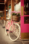 A nostalgic scene of an old fashion pink bicycle with a flower basket in the front. The bike is parked and leaning against the pink door of a retail shop along the pedestrian sidewalk. An old fashion retro scene of the past. Photographed in vertical format and processed with de-saturation and warm tone.