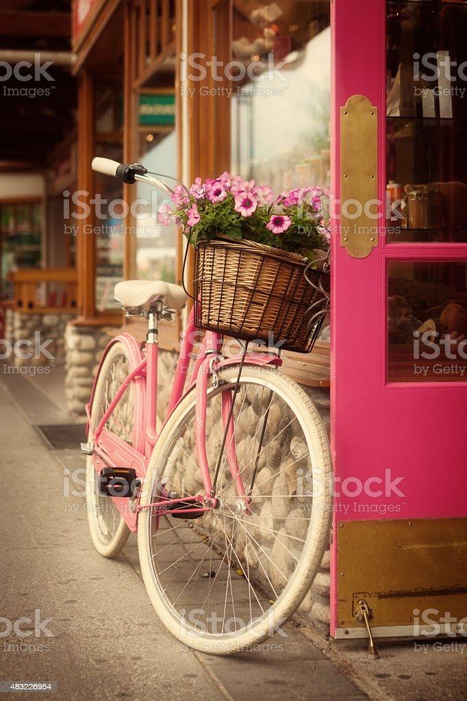 Color rosa con la cesta de flores en bicicleta de un rosa puerta frontal - foto de stock