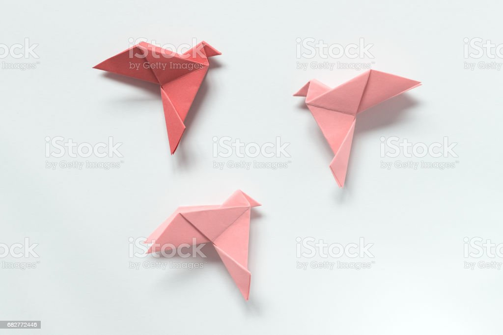 Pink Birds of different shades. Origami on light background. The concept of freedom, inspiration. stock photo