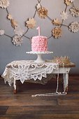 A pink birthday cake with a number one on top sits on a rustic, wooden stool. A crown and a string of pearls lay beside the cake. A party awaits a princess!