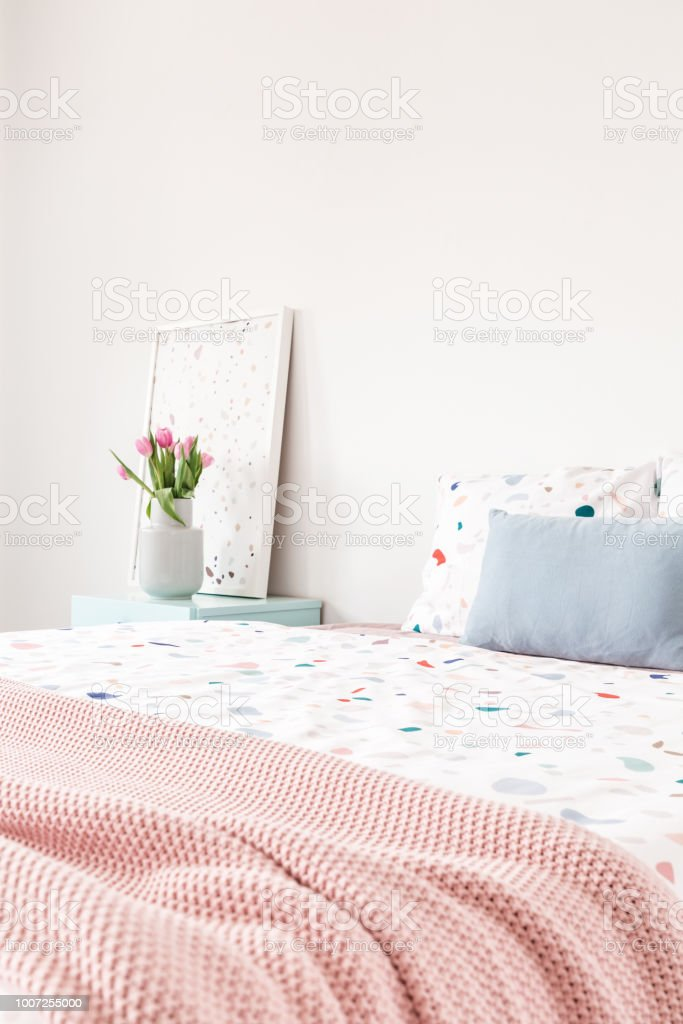 Pink Blanket On Bed With Patterned Sheets And Blue Cushion In Bedroom  Interior With Flowers Real Photo Stock Photo   Download Image Now