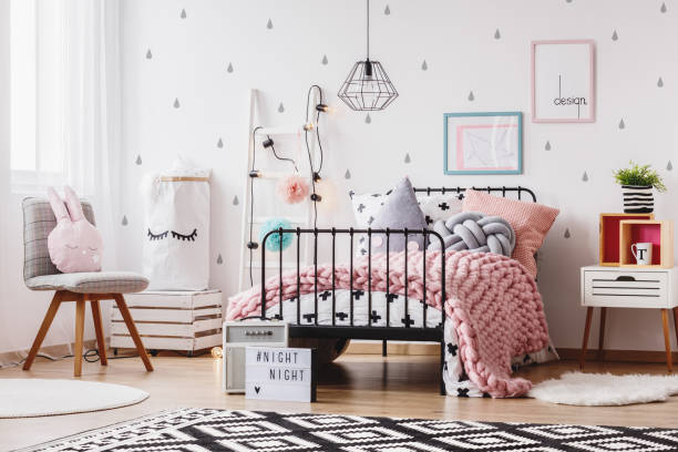 Pink blanket on girl's bed Pink knit blanket on girl's bed with pillows in colorful bedroom with ladder, chair and plant girl bedroom stock pictures, royalty-free photos & images