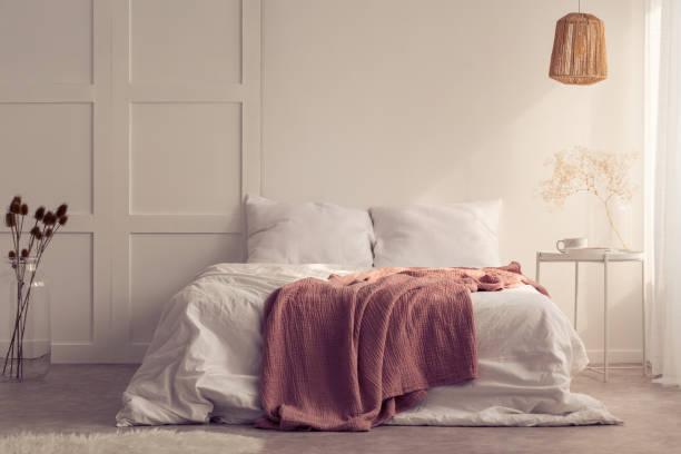 식물을 테이블 위에 램프와 최소한의 침실 인테리어에 흰색 침대에 핑크 담요. 실제 사진 - 침구 뉴스 사진 이미지