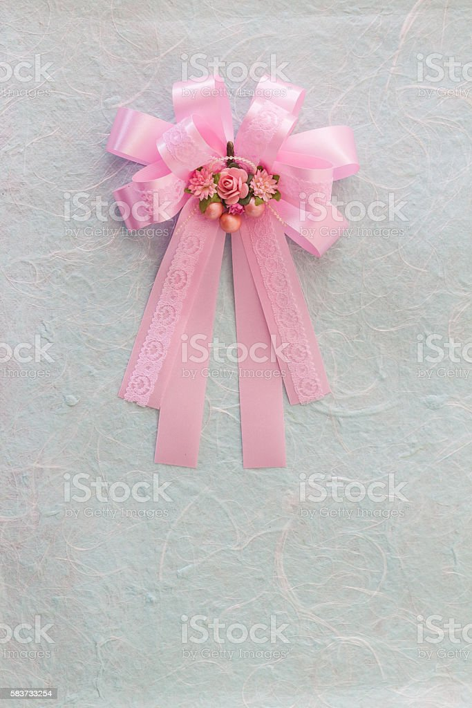 Pink bow with fabric flower on blue mulberry paper
