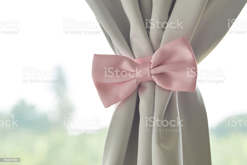 Pink bow tie beautiful modern grey curtains stock photo