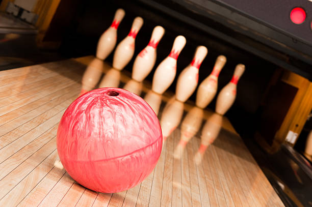 A pink bowling ball going toward pins stock photo