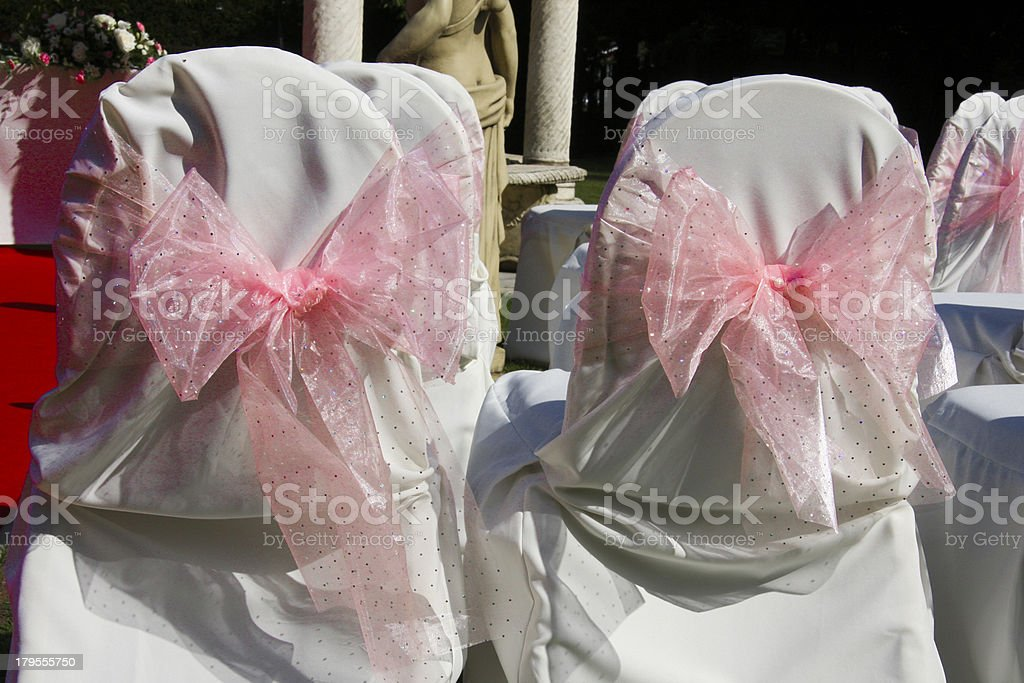 Pink bows on white chair covers wedding in hotel.