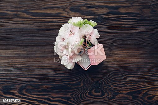 istock Pink box for engagement ring and hydrangea on wooden table, top view. 698197372