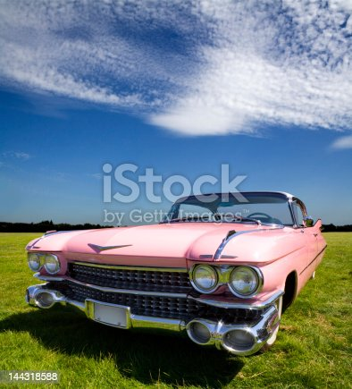 A classic 1959 pink Cadillac Coupe de Ville dream machine in dynamic full frontal.