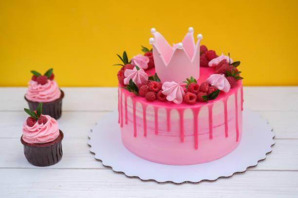 rosa kuchen mit krone auf geburtstag auf gelbem hintergrund - prinzessinnen torte stock-fotos und bilder