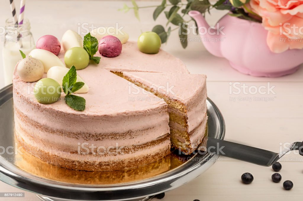 Pink cake with mint and decorative sweet balls from above on a plate, close-up stock photo