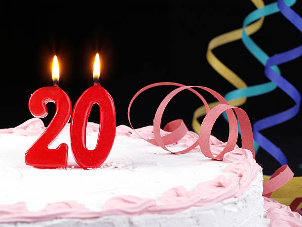 A pink cake with red number twenty candles stock photo