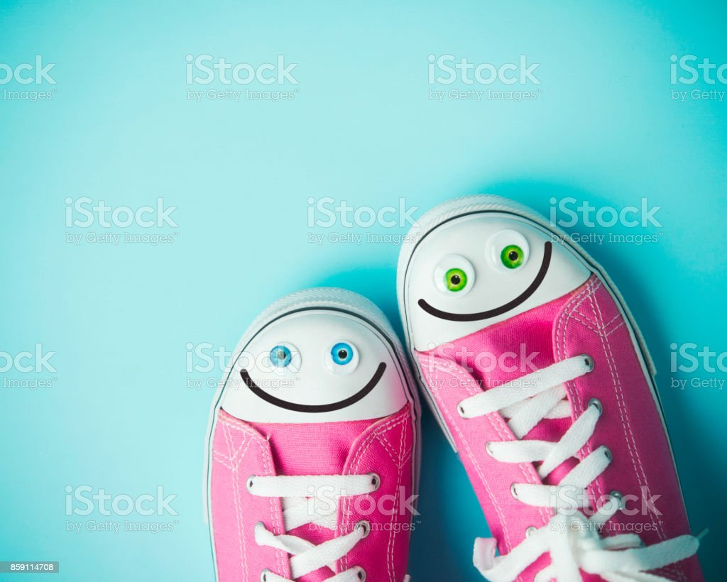 Pink canvas shoes with happy faces on blue background stock photo