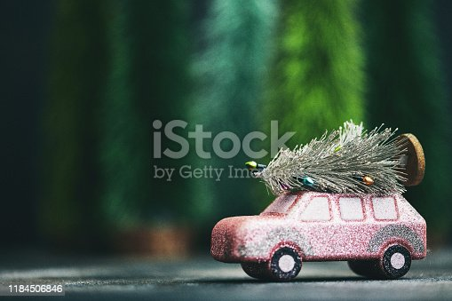 Pink car transporting Christmas tree. Christmas holiday background.