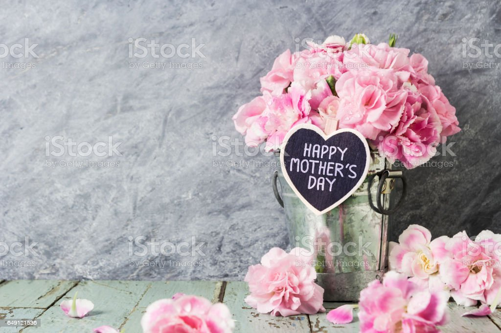 Pink carnation flowers in zinc bucket with happy mothers day letter on wood heart stock photo