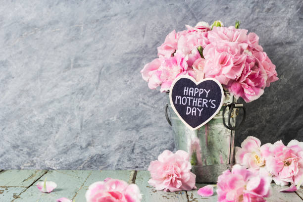 pink carnation flowers in zinc bucket with happy mothers day letter on wood heart - mothers day stock pictures, royalty-free photos & images