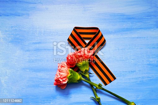 Carnation and St. George ribbon on blue background, symbol of the great Victory, victory day, 9 May background