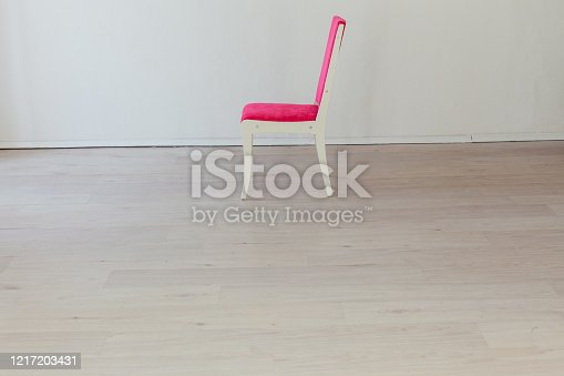 902720222 istock photo pink chair in the interior of an empty white room 1217203431