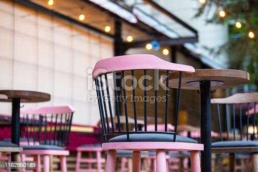 Outdoor pub with furniture on beautiful spring day,close up to pink chairs , no people