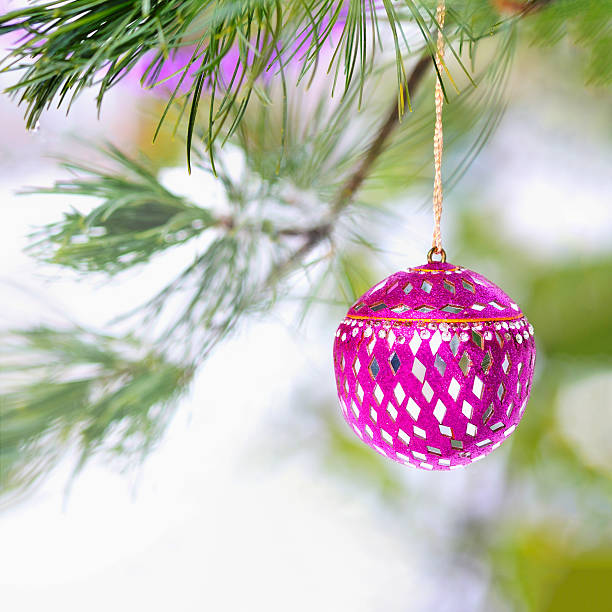 Pink Christmas ornament on snowy tree stock photo