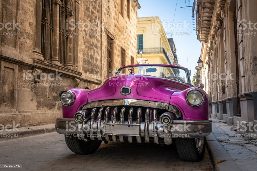A pink classic car parked on a street in Havana, Cuba.