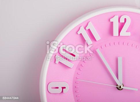 istock pink clock face closeup 534447044