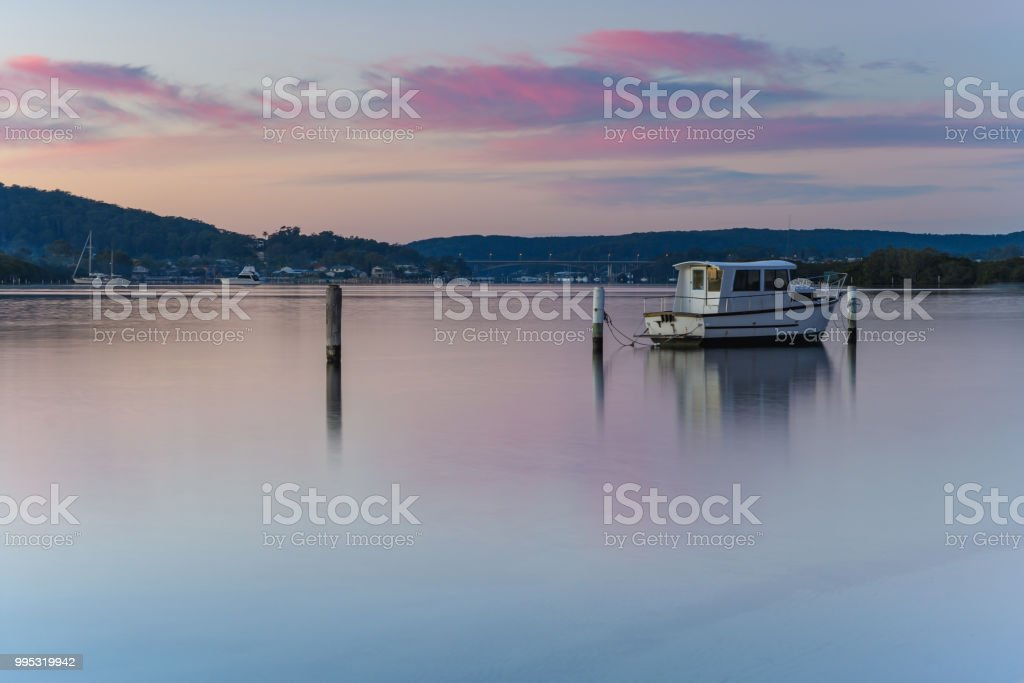 Pink Clouds and Boat on the Bay stock photo