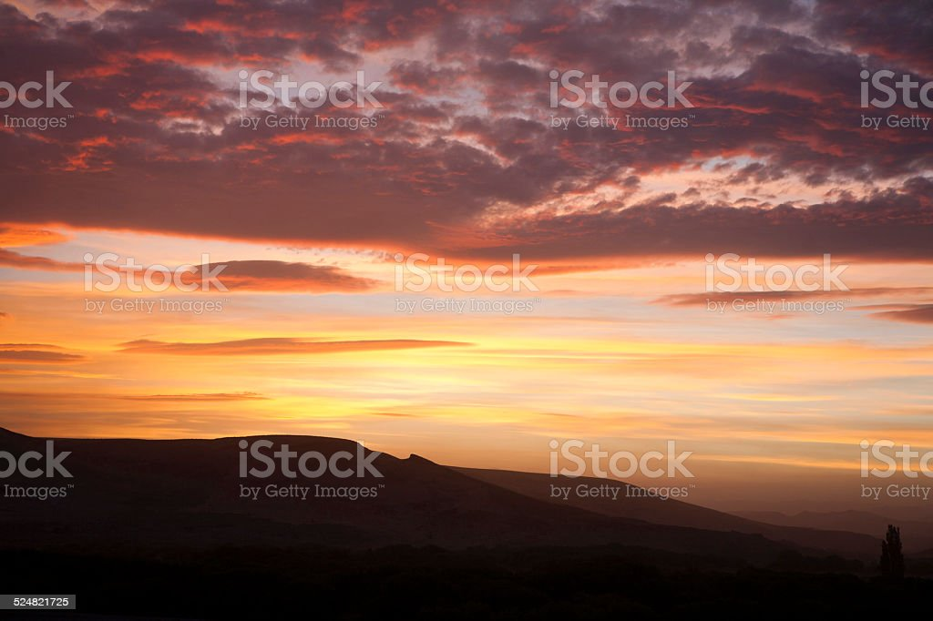 Pink clouds and orange sky over mountains stock photo