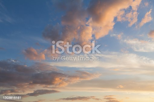 Beautiful clouds and blue sky background at sunset with pink and purple tones over England UK. Cloudscape and skyscape backdrop